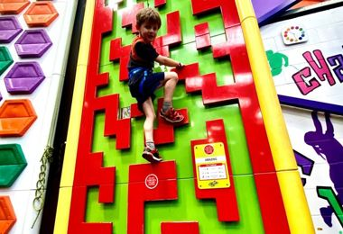 Pupil on red climbing wall