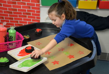 Pre-Prep girl making Christmas stamp artwork