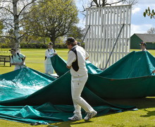 Cricket players preparing ground on top field
