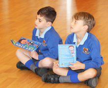 Year 2 boys reading first aid book Flat Stan