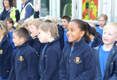 Year 1 pupils listening to fireman at fire station visit