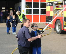Year 1 boy spraying with hose at fire station visit