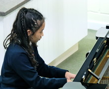 Girl on piano in 4th Form Concert