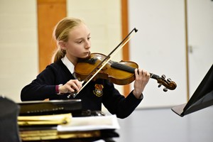 Violinist performing in Form 2 Concert