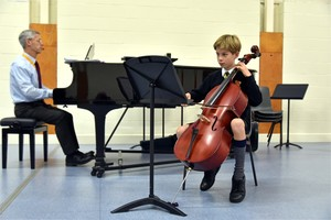 Form 2 boy playing cello in concert