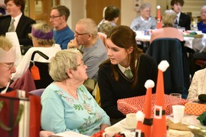 Pupil chatting to guest at OAP Xmas Lunch