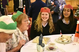 Sixth Former chatting to guests at OAP Xmas Lunch 18