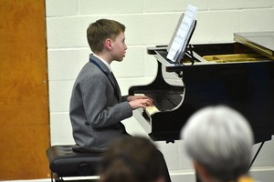 Boy on piano in Form 1 Concert Feb 19
