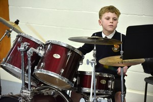 Boy drumming in Form 1 Concert Feb 19