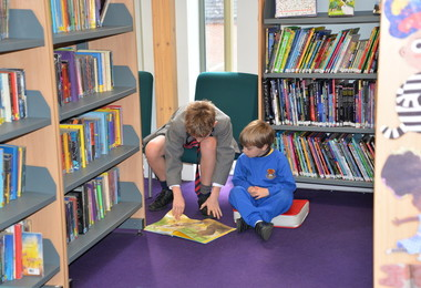L3 boy reads to Reception pupil on World Book Day
