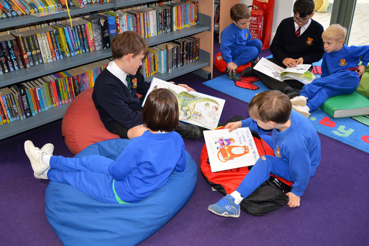 Reception pupils reading with L3 boy on World Book Day